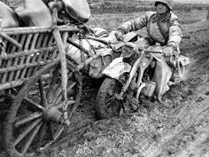 """A German soldier from the SS Division """"Das Reich"""", struggles with his BMW R-12 motorcycle in the Russian mud. (1941)."""