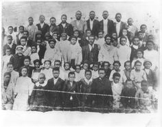 """Association43A.W. Jackson, Superintendent of """"Negro School,"""" Rosenberg, with students. Jackson is pictured at center in dark suit and tie. Five rows of students range in age from 1st grade through high school. Barbed wire fence runs across foreground of photo. Jackson was the 43th Colored Teachers' State Association  President"""