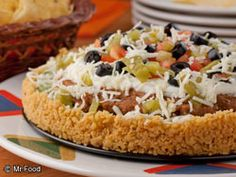 Fiesta of a Spread | mrfood.com a butter & corn chip baked crust with layered refried beans guacamole & goodies.