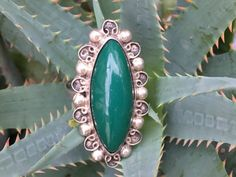 Vintage hand made sterling silver ring. Made in Mexico and set with green glass that they call green obsidian Face of the ring measures 1 1/2 by