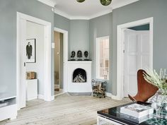 The grey-green walls in this home look so beautiful against the light wooden floor. The leather butterfly chair goes so perfectly with this tint and is a real eye-catcher in the living room. via 55 Kvadrat Green Living Room Paint, Light Wooden Floor, Green Wall Color, Living Room Decor Fireplace, Small Fireplace, Light Green Walls, Grey Flooring, Dream Decor, Grey Walls