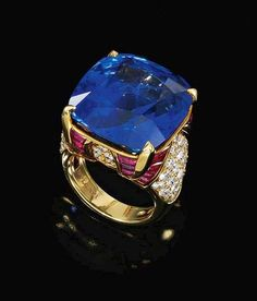 Lot 557~ Sapphire and Ruby, and Diamond Ring, BULGARI  Estimate: 145,000 – 190,000 CHF Centring on a Cushion-shaped Sapphire to a mount enhanced with buff-top Rubies and Brilliant-cut Diamonds, signed Bulgari.