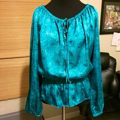 Michael Kors size S teal top gathered at bottom This shirt is a little more green than the pictures show! It can be worn on or off the shoulder. Tie at neck, gathered and blousy 3/4 way down. True teal color. Gathered at bottom of sleeves. Very nice top! Silky material! Looks new! Michael Kors Tops Blouses