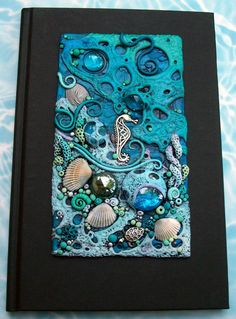 Coral Sea Journal Cover by MandarinMoon.deviantart.comThis is a custom order for a co-worker. The polymer clay piece is finished but I haven't attached it to the journal yet. I'm still not sure if I am going to paint the book itself. I'm still tossing around ideas. You all always have great ideas; what do you think?    Oh, the seahorse, turtle and the silver shell toward the top are all metal, there are three small real shells, glass gems and the rest was all made by hand out of clay.