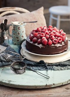 white cake with raspberry filling, chocolate icing, and fresh raspberries on top