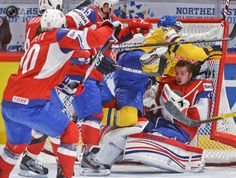 Norway's Haugen loses his helmet and is pushed by Sweden's Zetterberg and Spets, Holos and Tollefsen, during their 2012 IIHF men's ice hockey World Championship group B game in Stockholm.