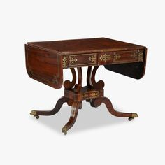 Regency brass inlaid rosewood sofa table early 19th century The drop-leaf banded top over two frieze drawers and opposing blind frieze drawers, raised on four scrolled supports above a shaped quadripartite gallery issuing four outswept legs on shell and claw cast casters. H: 28 1/2, W: 58 1/4, D: 26 in.