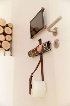Fin ide til både bladholder og toiletrulleholder. Fra Nybyggerne. Læderbælte med to skruer i.