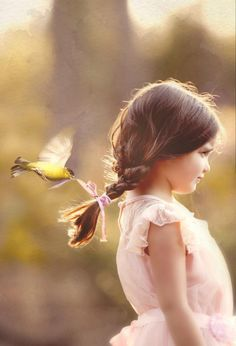 I like this, even though I'm almost 100% sure this is a work of Photoshop art. It's nicely done, and I'm now wondering if a little birdy has EVER mistaken a girl's hair ribbon for a likely piece of nesting material.