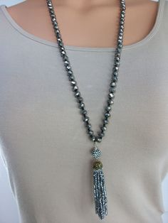 This is a beautiful hand knotted crystal beaded necklace done in colors that are fun and neutral enough to go with everything. The necklace has a gorgeous handmade beaded tassel as the focal point. This necklace is very versatile and will go with everything. Knotting each bead by hand