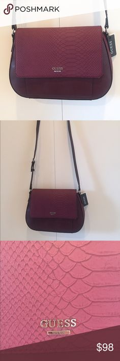 Guess Cross body bag New with tags in beautiful wine color.                     Measures about 13'in wide and 9.5 'in in height Guess Bags Crossbody Bags