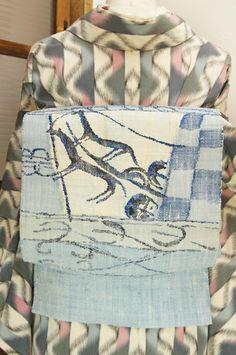 生成り色とパウダーブルー、ネイビーの糸で織り出されたグレーみをおびたどこか優しく愁いをおびた青の濃淡で織り出された、ソリを引く馬のようなモチーフがメルヘンチックな紬のつくり帯です。
