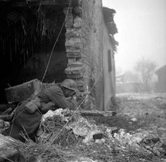 A British soldier 'firing on German positions' from a ruined house in the…