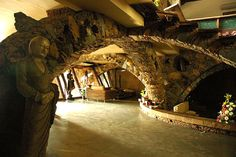 Interior view of the intersecting stone arches made from a variety of chipped stones, large boulders, and terracotta pots | Archnet