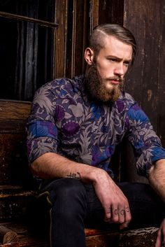 Great man's grey, black, blue, & purple shirt supported by such suave expression, beard, & masculinity.