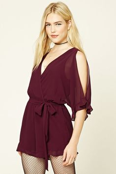 A chiffon woven romper featuring open shoulders, a surplice neckline, short vented sleeves, a buttoned slit back, an elasticized waist with self-tying sash, and ruffed trim.