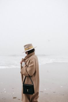 Fashion blogger Beatrice Gutu beautiful photography fashion editorial at the sea in a camel oversized coat