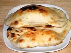 "Naan is the most popular Indian bread in the Western world. It is a flat bread that is traditionally cooked in a clay oven or ""tandoor."" This recipe however uses a regular home oven (with a pizza stone). Serve Naan with Daal, Chola, Palak Paneer or any vegetable dish."