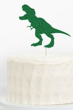 This green sparkly T-Rex cake topper is just what you need to turn a regular frosted cake into a show stopper. Create a dinosaur-themed birthday cake with no effort and in no time! See more party ideas and share yours at CatchMyParty.com Dinosaur Party Decorations, Dinosaur Party Supplies, Dinosaur Party Favors, Diy Party Supplies, Dinosaur Birthday Party, Dinosaur Cupcake Toppers, Dinosaur Cake, Dinosaur Photo Booth, T Rex Cake