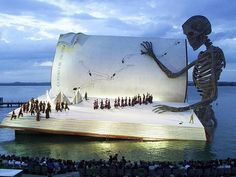 "How cool is this?!!  Floating Stage of the Bregenz Festival (Austria); Verdi's opera ""A Masked Ball"" in 1999 featured a giant book being read by a skeleton."