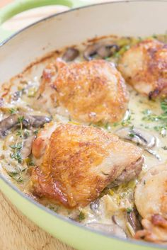 Golden Brown Seared Chicken Thighs In A Green Le Creuset Enameled Pan With Parmesan Mushroom Leek Cream Sauce And Sprigs Of Fresh Thyme