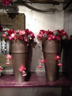 Kerst - 2 bronskleurige grote potten met roze bloemen en wat hangende kerstballen opgemaakt! Naar voorbeeld van Jan Cees Lont, sfeerboerderij in Oude Niedorp