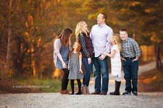 big family of six laughing on a dirt road during a fall portrait session by Atlanta family photographer