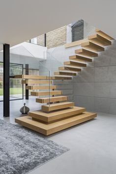 A staircase made of open oak treads and laminated low iron glass balustrade offers a floating look. Wooden Staircase Design, Home Stairs Design, Stair Railing Design, Floating Staircase, Wooden Staircases, Modern Stairs Design, House Staircase, Interior Staircase, Staircase Railings