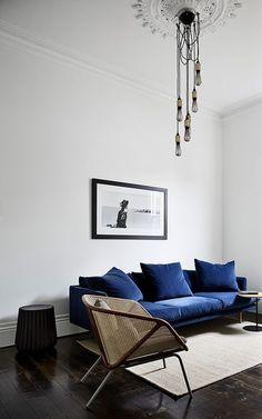 Entre un canapé en velours et une assise en cannage, le salon aime mixer les matières