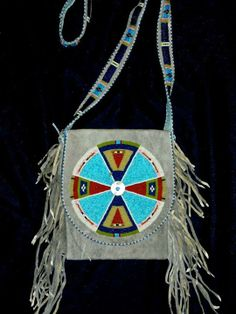 """The Corner Mercantile, """"Indian Goods' and authentic Indian Trading Post Vintage hunting pouch or shoulder bag, with traditional old style pattern. sewn with antique size 12 beads, moonshell conchas and brain tanned buckskin painted a """"worn blue"""". 8' long, 6 1/2' wide and the lined and beaded strap is 18' long"""