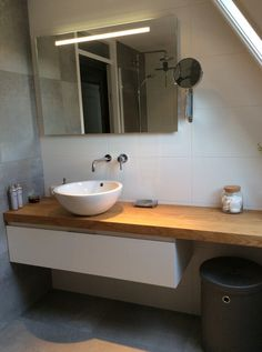 Sfeervolle badkamer: mooie grijze tegels in combinatie met een prachtig houten blad met opzet waskom en witte onderkast.