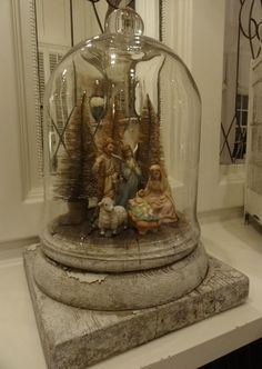 Nativity under cloche (sans trees?).  Aged wood base.