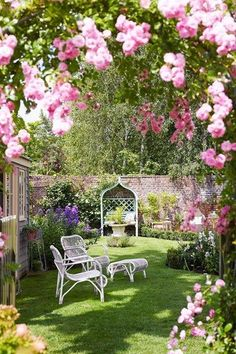Small city garden in country style with rose arbour and white outdoor seating.