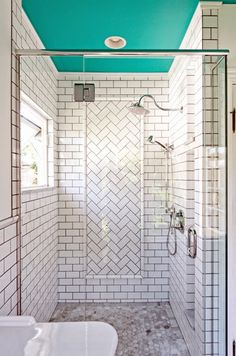 White subway tile in bathroom with glass shower and painted turquoise ceiling