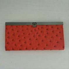 Femina Ostrich Embossed Clutch Wallet Femina Ostrich Embossed Clutch Wallet in Orange. Has latch closure, four expanding pockets with card slots, one zipper pocket. Femina Bags Wallets