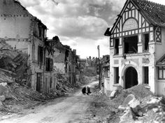 Two French women carry their belongings down the ruins of rue Paul Doumer in Caen following the British and Canadian liberation of the city after the Battle for Caen, part of the larger Battle of Normandy. Caen, Calvados, Lower Normandy, France. August 1944.