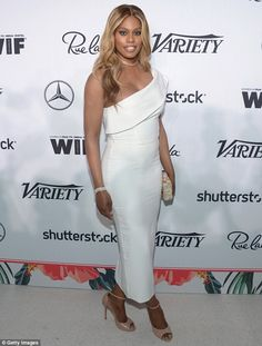 Laverne Cox wears an off the shoulder white dress and blue jumpsuit
