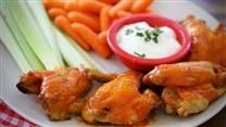 Let the slow cooker do the main work of making spicy, buttery hot wings to serve during the game. The wings are finished in the oven and brushed with more sauce for serving. Great with ranch or blue cheese dressing.