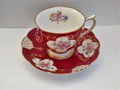 A Royal Albert teacup and saucer set The design is similar to the Georgina design by Royal Albert it has a countess cup shape It is in excellent condition The saucer has a dimeter of 14cm The cp is 7cm high with a top diameter of 8cm Its main cour is red / dark rose gold rim and