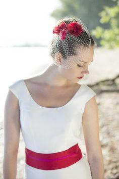 brautkleid mit trägern, überschnittenen schultern und rundem ausschnitt, gürtel mit rot und pink, leicht ausgestellter rock in a- linie, fascinator mit roten und pinken fächerblumen und hutschleier (Foto: Hanna Witte) (http://www.noni-mode.de)