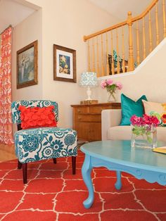 LOVE the bright colors with pops of teal, turquoise,coral and orange in this neutral wall living room!