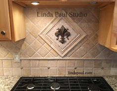 Buy this Fleur de lis mini medallion from Linda Paul Studio - Comes in 19 metal colors and 7 choices of stone colors. Shown here is bronze antique patina finish with S3 and S5 travertine mosaic stone tile. The customer surrounded the medallion with stone chair rail. There are also some Clavo accents added to the backsplash area. Using the field stone in 2 directions with a small border to separate adds interest to the space. Just a small accent can make a big splash!