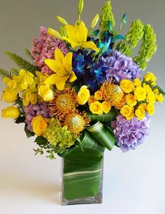 Brilliant Elegance-This beautiful design of yellows and blues features our leaf-wrapped signature clear vase overflowing with lilies, roses, and hydrangea among other floral textures and elegant greenery which completes a top of the line look. Perfect for the Home or Office. #StadiumFlowers #MardiGras #MardiGrasFlowers
