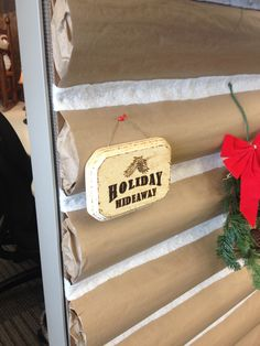 """A wood-burned sign identifies the log cabin as the """"Holiday Hideaway."""""""