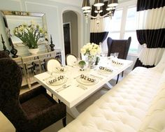 Custom striped silk drapes, tufted banquette, glossy white dining table, louis chairs, mirrored buffet