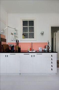 Een oudroze kleurbalk en zorgvuldig uitgezocht servieswerk fleuren de sobere keukenkasten op een subtiele manier op.