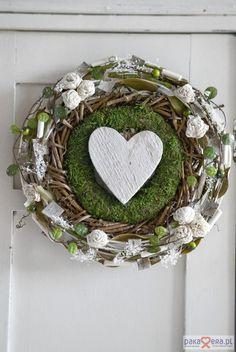 Zielony wianek opleciony został naturalnymi oplotami oraz wybielanym ratanem.  Elementy dekoracyjne doklejone do wianka to wybielany susz, kremowe kwiatki sola, gałązki z zielonymi listkami, kawałki kory brzozy   oraz zielone kuleczki.  Centralnym elementem wianka jest drewniane serduszko  Wielk...