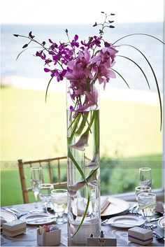 Centerpiece idea-- I would do orange or yellow flowers but the tall vases are pretty!