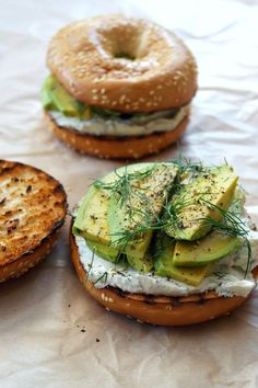 Avocado topped bagel with cream cheese and thyme.