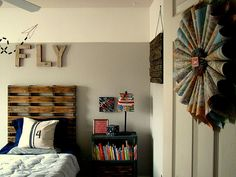 Love everything about this boys Vintage Airplane Bedroom - from the map wreath on the door to the funky reclaimed fence turned wall art